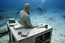 Underwater sculpture of a man sitting at a desk. Photo © Jason deCaires Taylor.