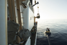 Derelict fishing nets are craned onboard the NOAA Ship Sette to transport back to Honolulu