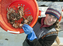 Anna Mercer holding up a basket of jonah crabs