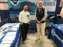 Two representatives from NOAA Fisheries table at a saltwater fishing show.