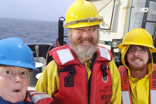three scientists in life jackets and hard hats on the deck of a research vessel