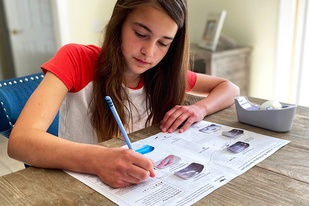 A young female coloring a educational map-making fish habitat activity.