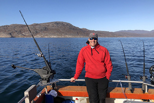 Salmon scientist Tim Sheehan waits patiently for Atlantic salmon to take the bait from several fishing poles on the M/S Vange II