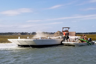 Substrate is moved off a boat to form an oyster reef.