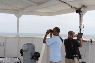 Observer with binoculars and another recording data on computer on ship's flying bridge