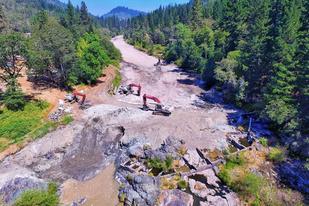 Aerial photo of two backhoes in a river valley