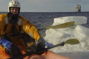 Man in protective gear in a sea kayak near ice, ship in background