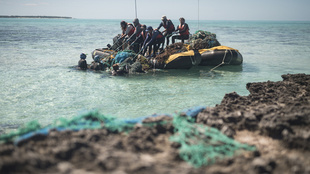 The team pulls a large mass of nets into the boat near the barrier reef at Midway Atoll