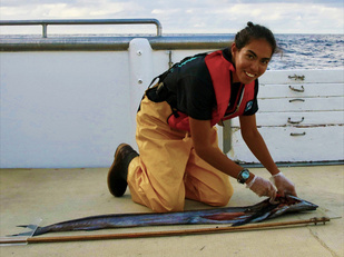 Pacific Islands observer Holly Naholowaa collecting samples from a lancetfish.