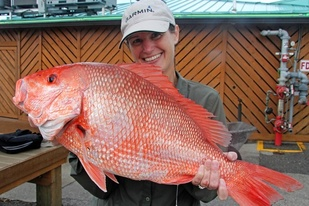 A smiling woman holds a large red snapper.