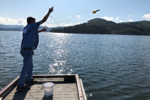 A Veterans Corps participant in Oregon tosses a sampling bottle into the water.