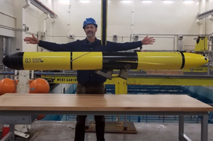 A scientist with an arm span of 6 feet stands with a glider. The gliders are approximately 8 feet long and weigh around 200 lbs.