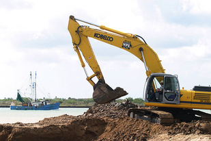 An excavator scoops up soil while a shrimping boat passes in the background