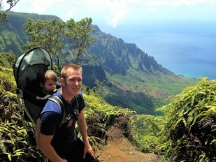 Glenn Chamberlain with son in carrier on his back hiking in mountains in Hawaii