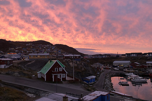 Dawn skies shimmer with pink and peach over the town harbor of Qaqortoq, Greenland.