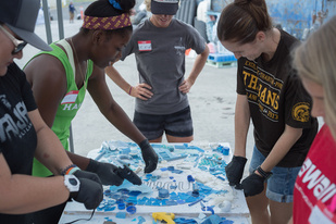Local students and teachers use pieces of marine debris to create a NOAA logo mosaic