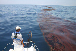 A man on a boat looks out at an oil slick