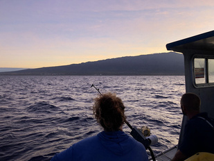 Melanie Hutchinson and fisherman Rick Reger watch the sun come up after a long night of fishing.