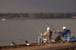 Two seated men fishing and chatting at Great Marsh Park in Cambridge.