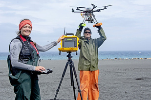 Katie Sweeney and Brian Fadely work with unmanned aerial system on Bogoslof Island.