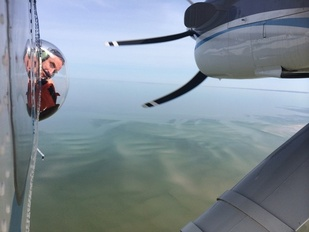 "Tim Cole looks through the ""bubble window"" of NOAA's Twin Otter plane"