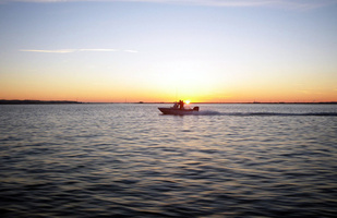 Anglers motoring a boat in California's Sacramento Delta at sunrise.