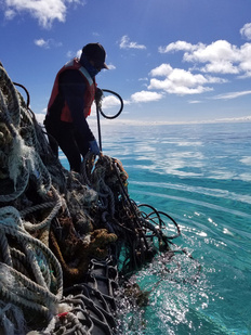 One of our team members, Mike, adding a floating net to our already massive pile of nets in the boat.