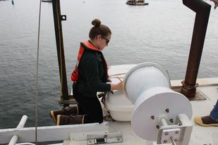 Observer on top of a fishing vessel's wheelhouse checks the life raft.