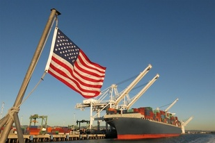 US flag and cargo ship at port.