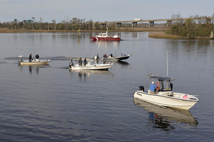 Four fishing boats float on the river with a red fire department boat behind them and a bridge in the background