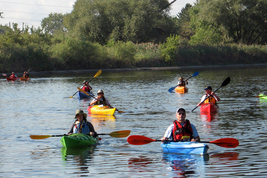 People kayak on the Detroit Rouge River.