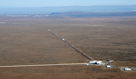 "A view of the LIGO detector in Hanford, Washington. A single laser beam is split in two and each half travels along one of two perpendicular, 2.5-mile long ""arms"" that form the interferometer's characteristic ""L"" shape. A mirror at the end of each path reflects each beam back toward the original source, where the beams recombine and enter a light detector. When a gravitational wave passes, the lengths of the arms change by a minuscule amount, causing the recombined beam to flicker. LIGO's light detectors record this oscillation, enabling the LIGO team to reconstruct the shape and strength of the incoming gravitational wave. Photo: NSF. (Click to download hi res version.)"