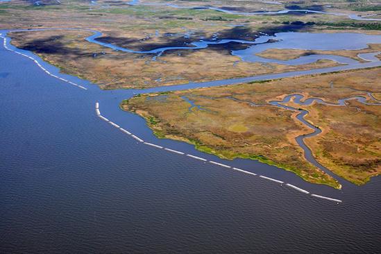 Aerial view of marsh shoreline lined by oyster reefs
