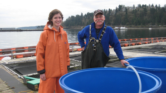 Manchester Research Station scientists standing next to net pens
