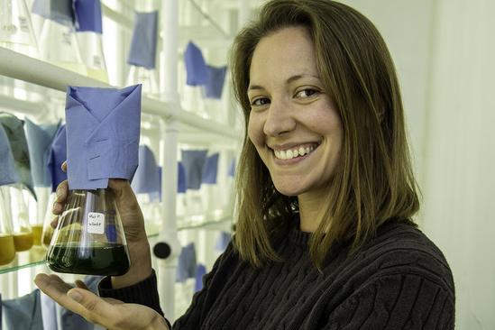 Lisa Guy holds a flask of algae.