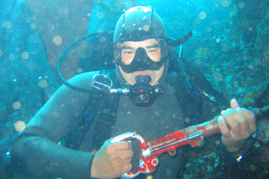 Diver in open water with full wet suite, holding tool.