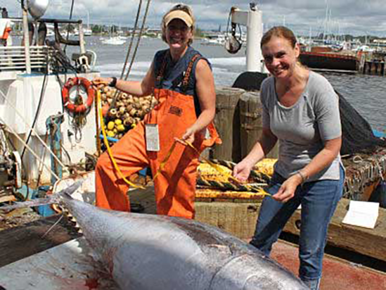 Amy measuring tuna on a fishing vessel