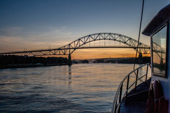 View from boat deck in the Cape Cod Canal with Bourne Bridge and a sunset in the background