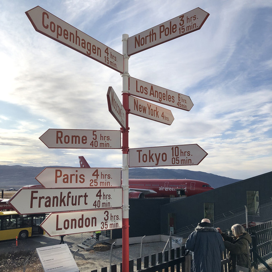 Sign post outside Kangerlussuaq Airport in Greenland showing direction and time difference of different locations around the world.