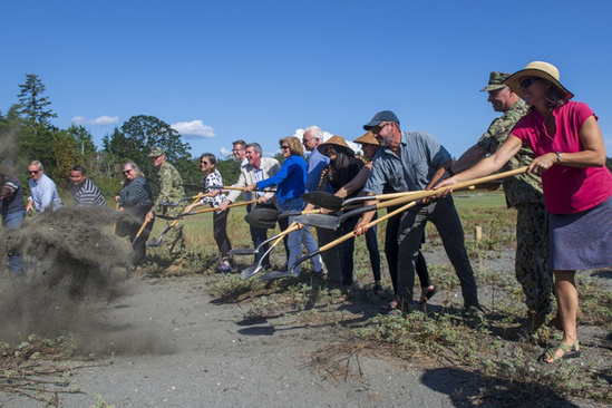 A large group of people holding shovels smile and toss dirt into a pile