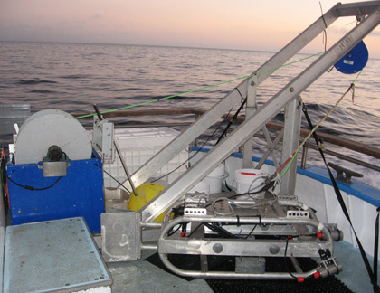 A metal a-frame and sled are shown on the back deck of a boat