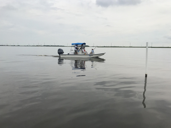 Personnel from NOAA Habitat Conservation Division, NOAA Restoration Center, and Louisiana Department of Wildlife and Fisheries measuring water depths at the West Louisiana Highway one marsh creation project. (photo credit.jpg