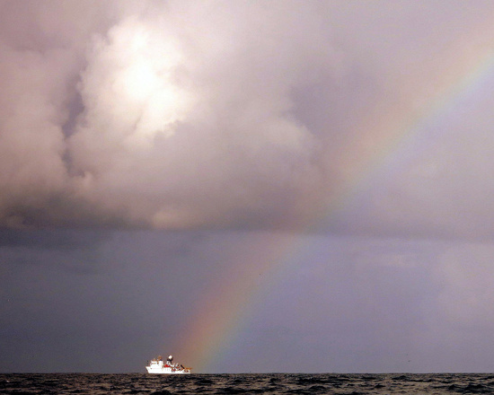 NOAA Ship Hiialakai sails under a rainbow