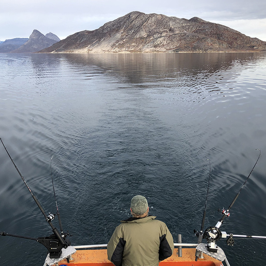 Commercial fisherman looks from the back deck of the fishing boat at the mountains looming high above Qaqortoq fjord in Greenland.