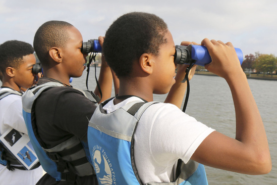 Children looking through binoculars as they learn more about environmental conservation.