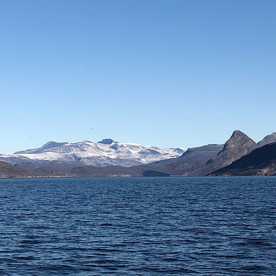 Snow-capped mountains along the Qaqortoq fjord, Greenland.