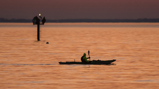 An intrepid kayaker is enjoying an early season sunrise paddle in Annapolis, MD.