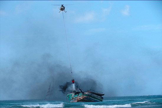 A Fire Department helicopter pours water onto a burning vessel in the water.