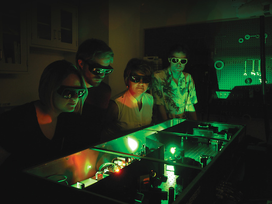 (L-R) Chemistry graduate students Hannah Ogden and Paul Diss, Professor Amy Mullin and Intern Augustus Cooke-Nesme (University College London) inspecting their laser system that generates highly excited molecules. Photo: (L-R) Chemistry graduate students Hannah Ogden and Paul Diss, Professor Amy Mullin and Intern Augustus Cooke-Nesme (University College London) inspecting their laser system that generates highly excited molecules.