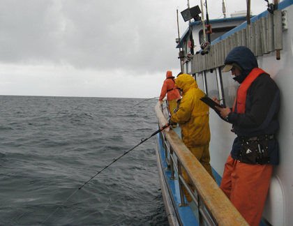 Scientist writing on a clipboard next to two men fishing